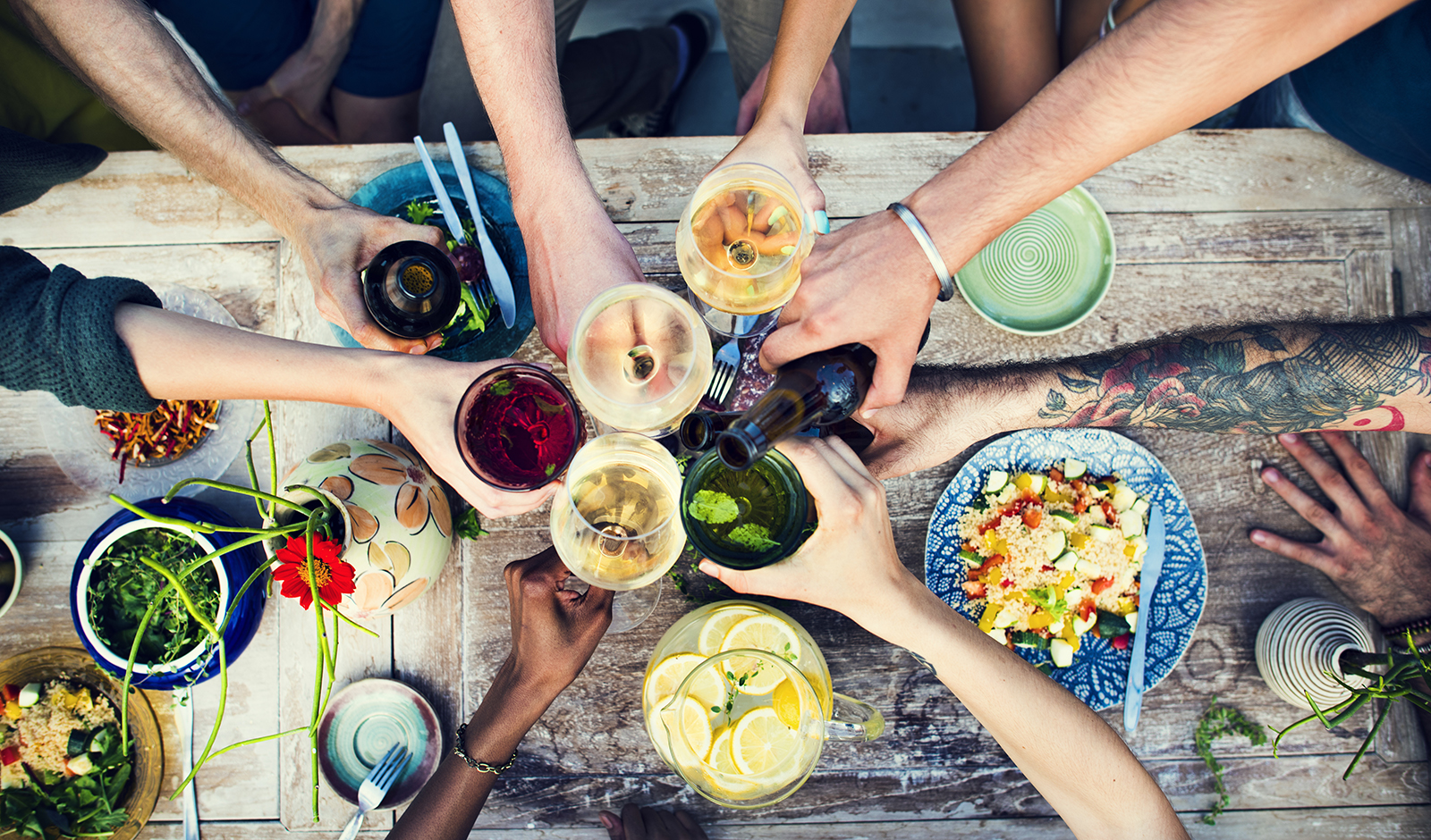 friends-toasting-over-vegan-food-over-picnic-table