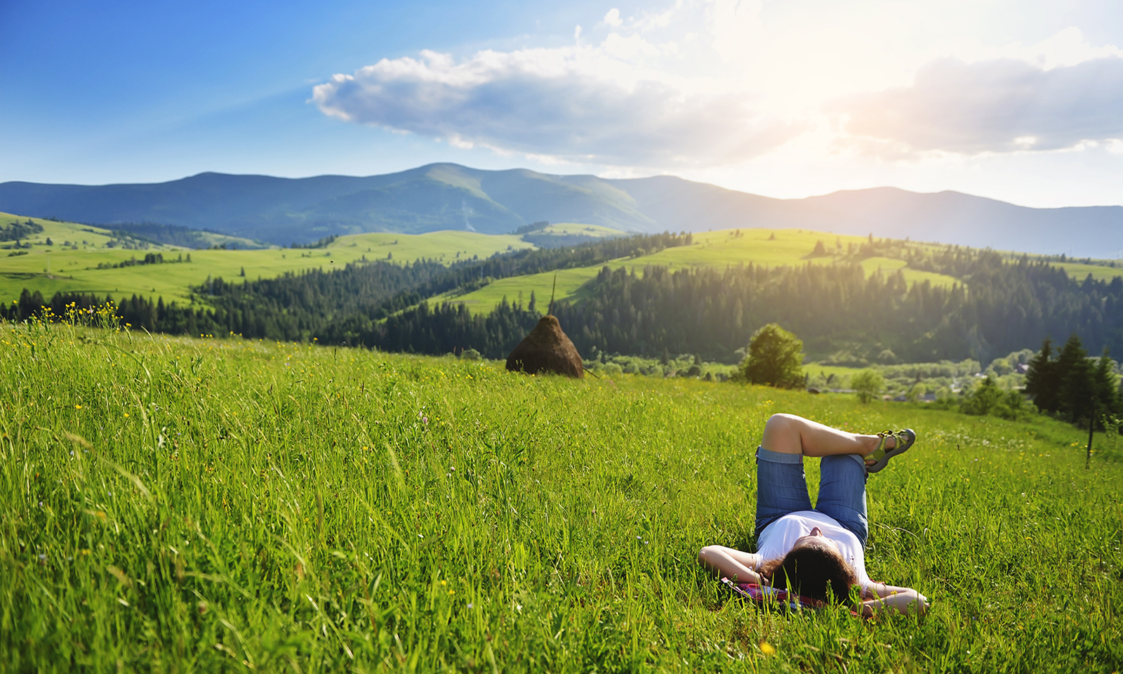 person-sitting-with-arms-back-and-legs-up-in-the-grass-looking-at-sky-serene-peaceful-calm
