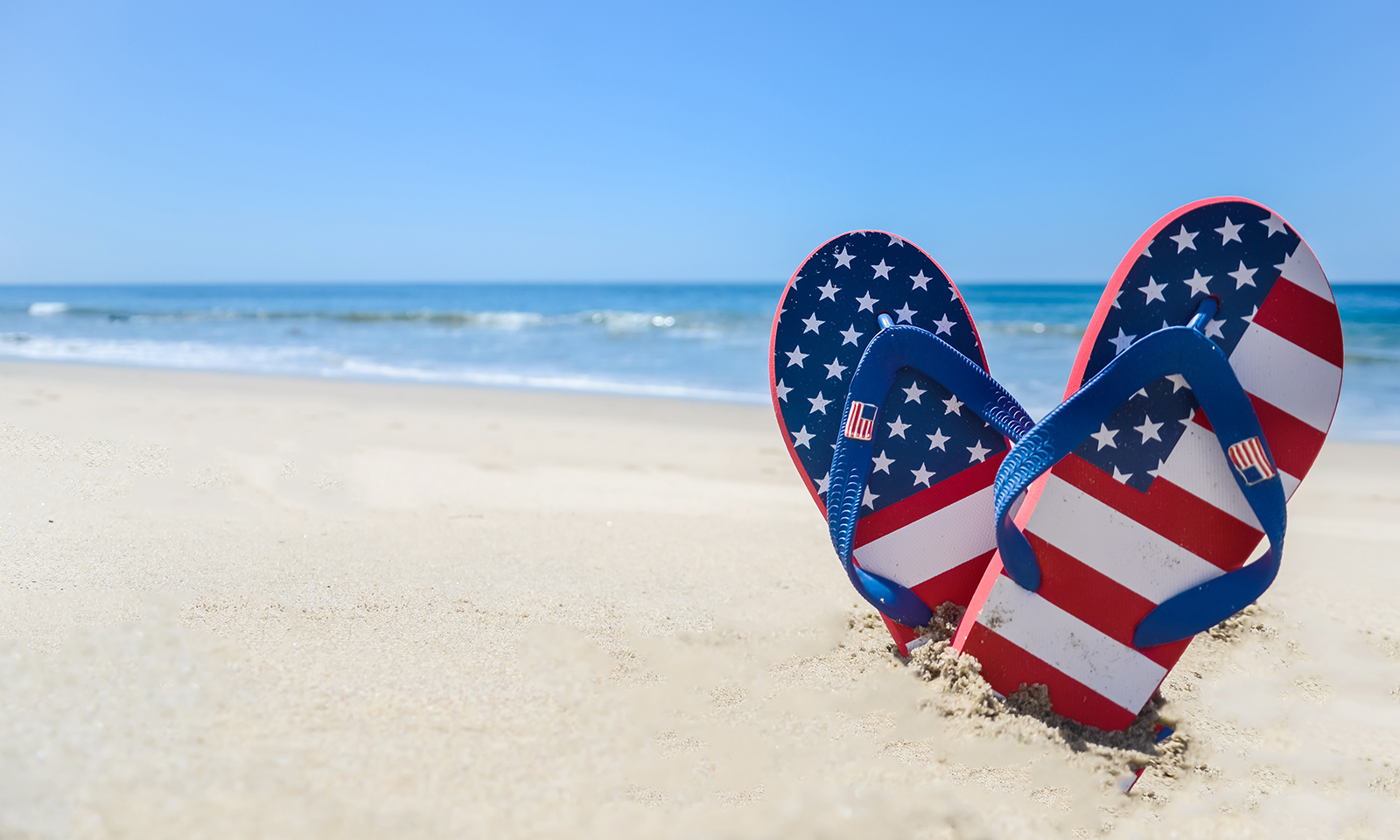 sandals-making-heart-shape-in-the-sand-on-the-beach