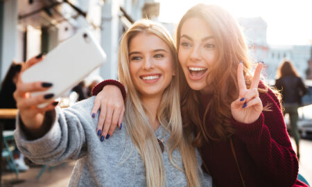 two-friends-taking-a-selife-holding-up-peace-sign