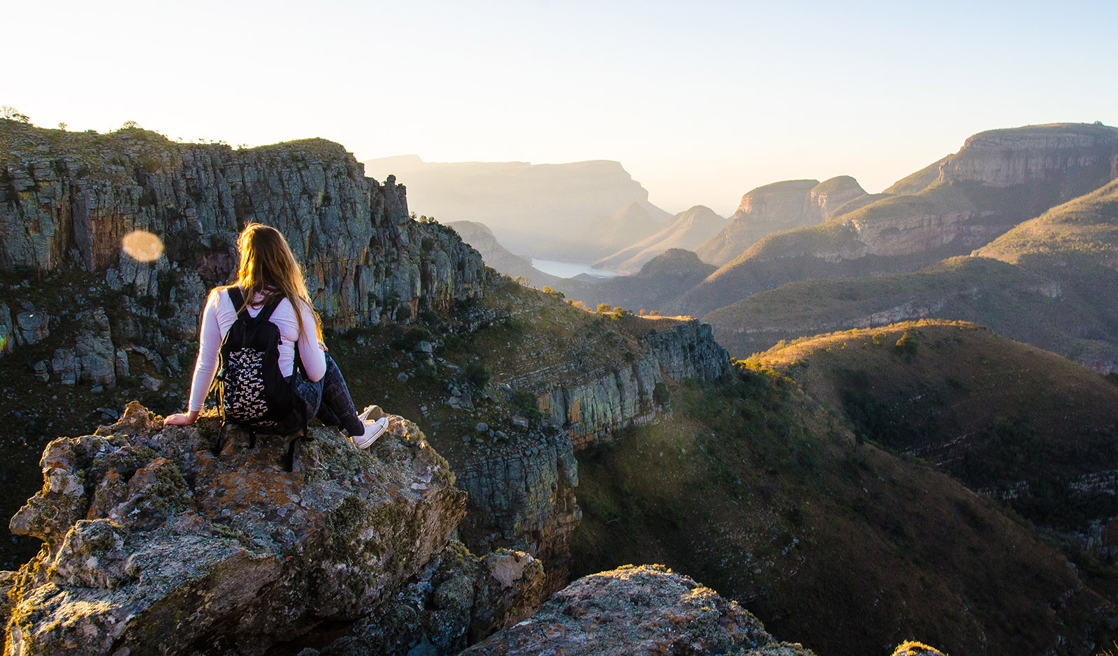 woman-sitting-over-ridge-in-nature-backpack
