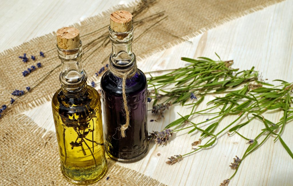 one small bottle of yellow-colored oil wit a herb infused beside a small bottle of purple-colored oil on the right are several pieces of lavender stems behind two brown colored strips of mat white background, essential oils for nasal congestion, 7 Essential Oils that Can Relieve a Stuffy Nose