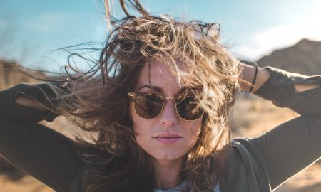 beautiful woman with a messy brown hair wearing aviator sunglassed and black jacket, ways to tame static hair, Ways to Tame Static and Fly Away Hair