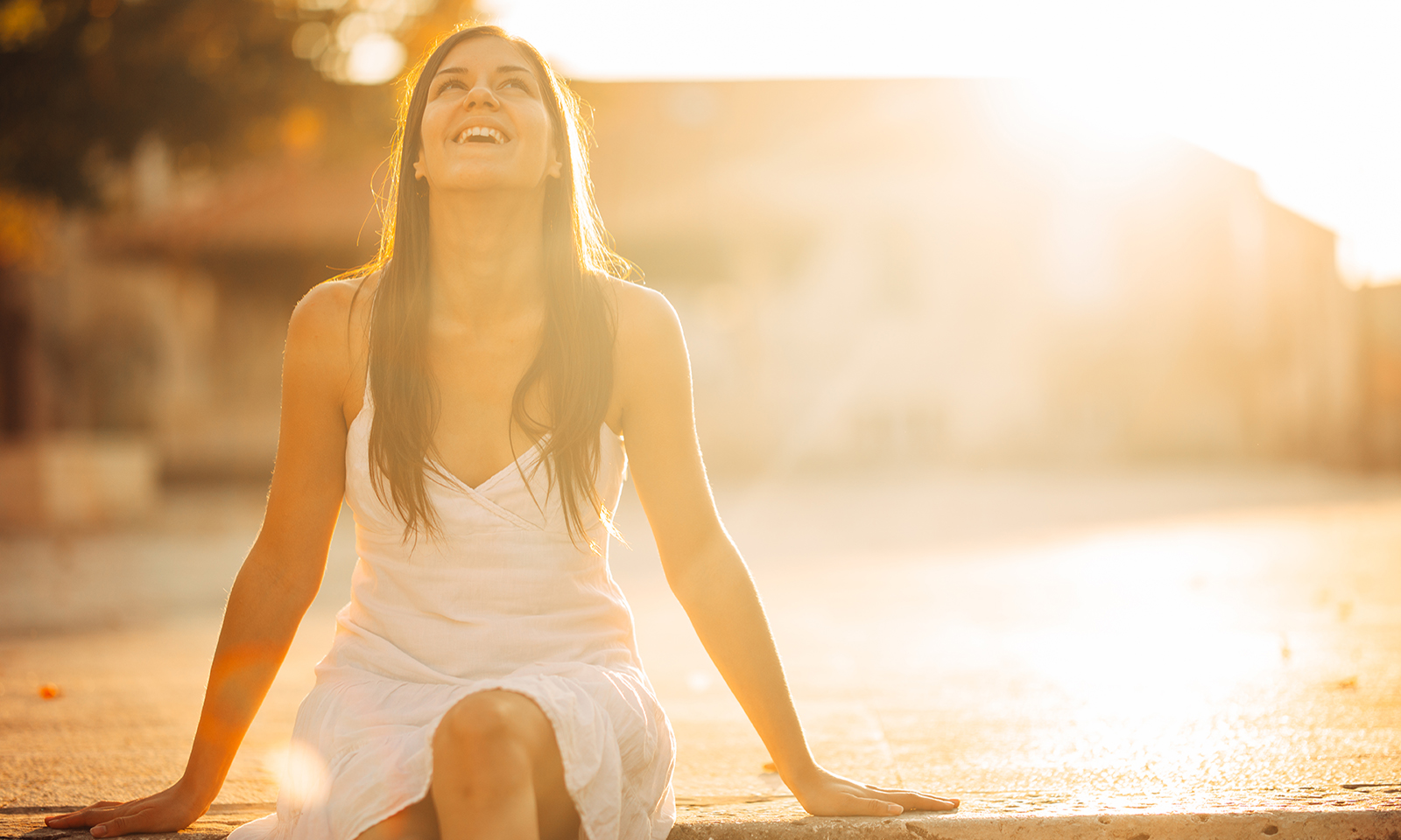 woman-sitting-on-pier-looking-up-in-the-sunlight