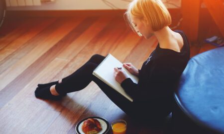 woman-sketching-in-a-pad-while-sitting-on-the-floor