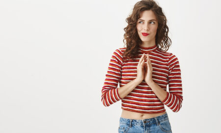 woman-thinking-and-holding-her-hands-together-in-red-and-white-striped-shirt