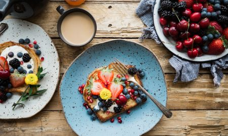a cup of creamy coffee on the top two plates with a toast topped with strawberries, blackberries, blueberries, and cherries top right bowl of different berries on top of brown wooden counter, Anti-Inflammatory Foods to Add to Your Diet