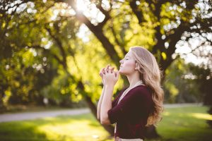 woman with long blonde hair wearing magenta blouse praying in a park with many trees, benefits of meditation, 7 Meditation Benefits that Will Improve Your Life