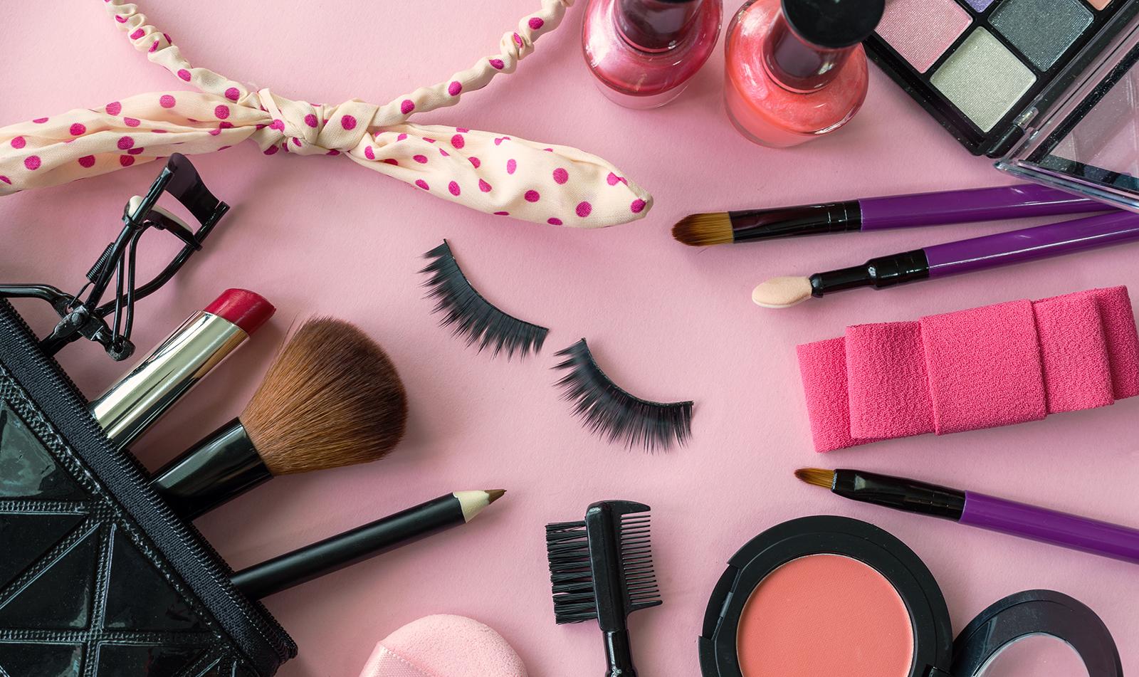 makeup-kit-makeup-items-laid-around-a-pink-background