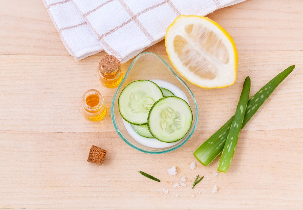 white towel on top below are two small vials filled with olive oil glass container with sliced cucumbers half sliced lemon two aloe vera leaves light brown background, natural ingredients for skin The Best Natural Ingredients You Can Add to Your Skin Care