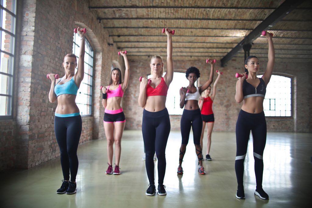 Group of women wearing colorful fitness attire doing dumbbell workouts