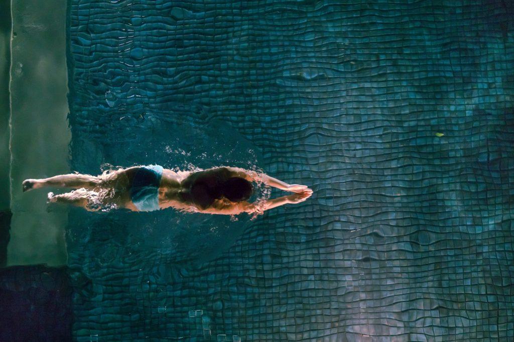 fit woman wearing blue bikini swimming in a pool