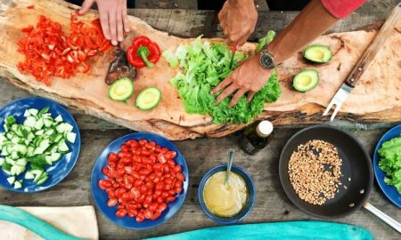 person chopping leafy greens surrounded by various plates of plant-based foods, chopped red bell pepper, and avocado, ways youre making veggies less health, 8 Ways Youre Making Your Veggies Less Healthy