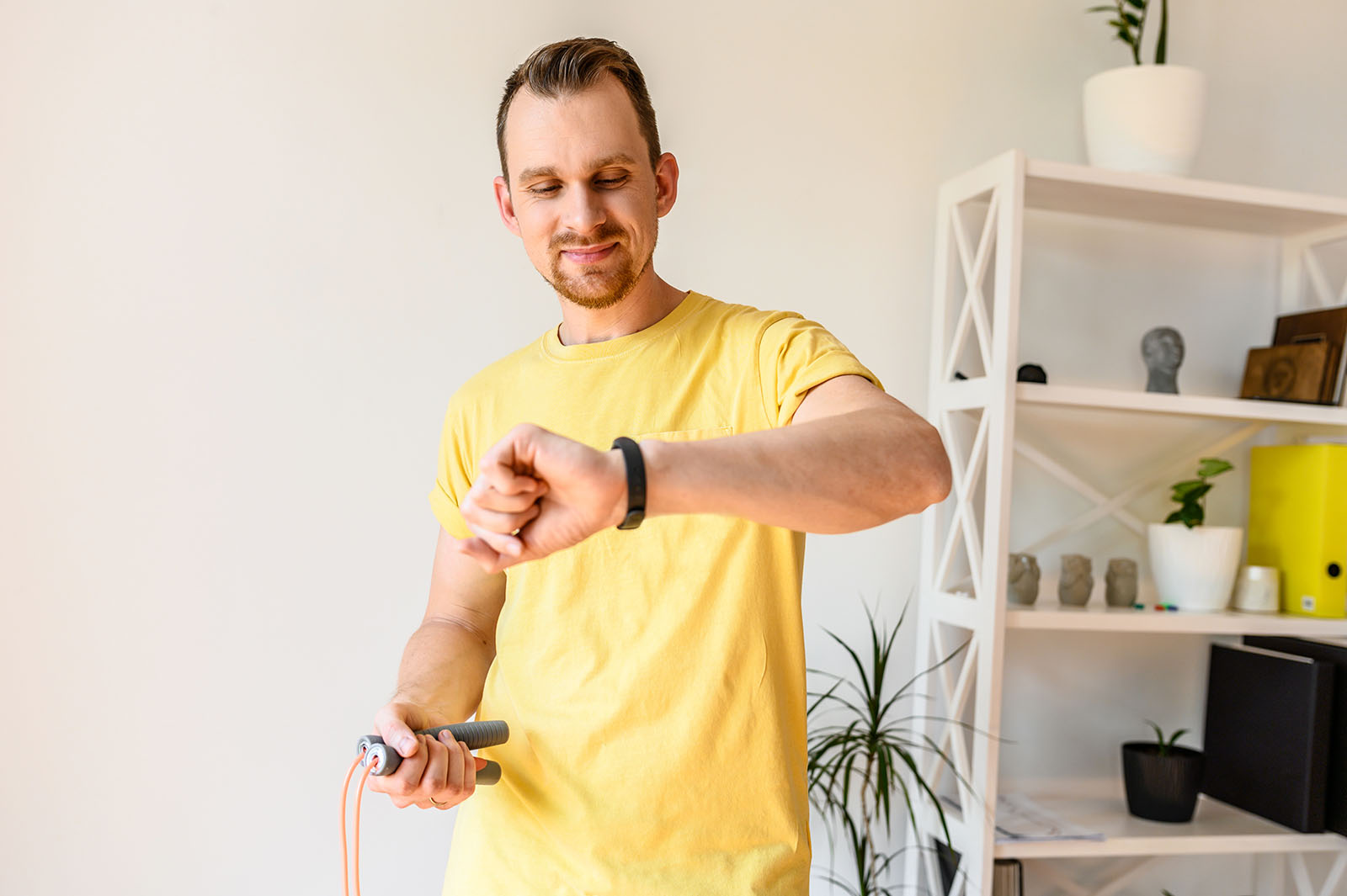 A guy with a jump rope looks at a fitness tracker