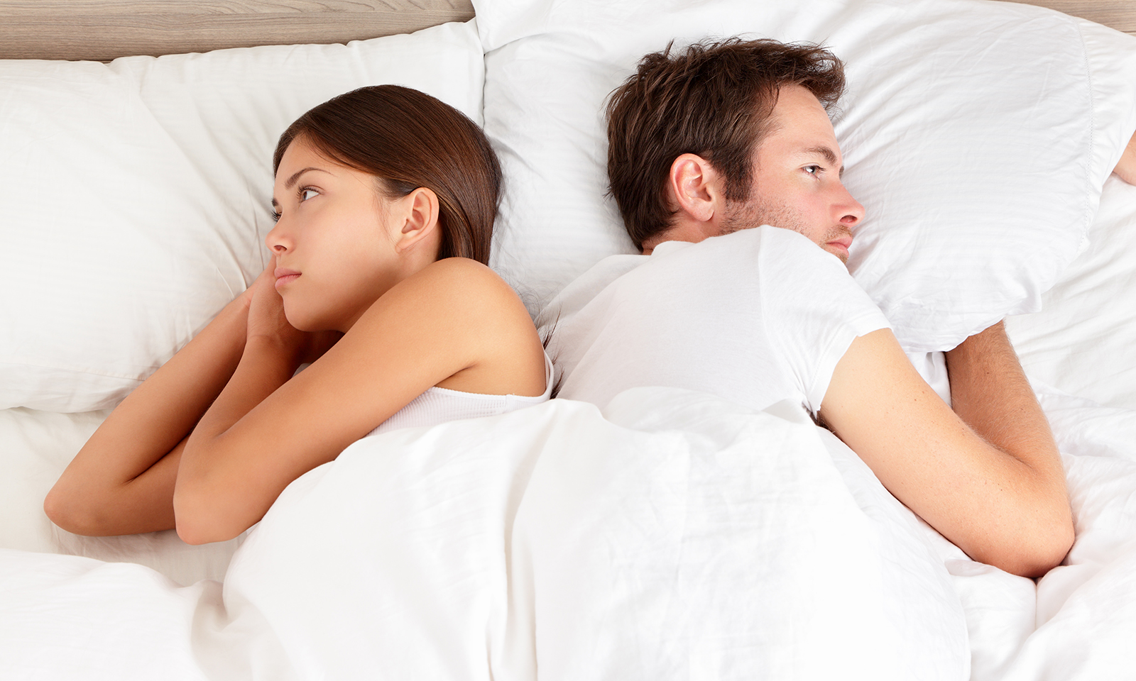 how-long-does-it-take-to-get-over-a-breakup-couple-looking-upset-in-bed