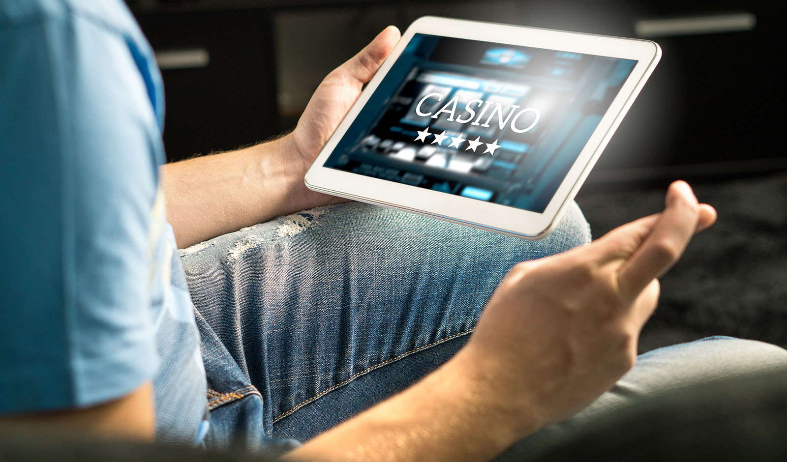 Excited man playing in an online casino with tablet fingers cros