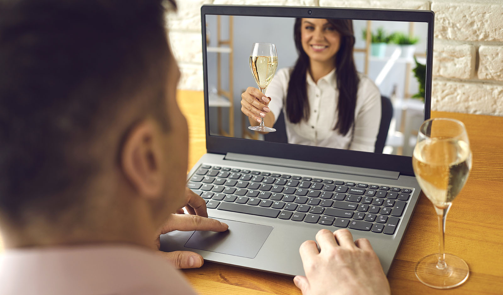 Date online. Loving couple with glasses of wine on a date distance using a video call laptop in a romantic setting at home.