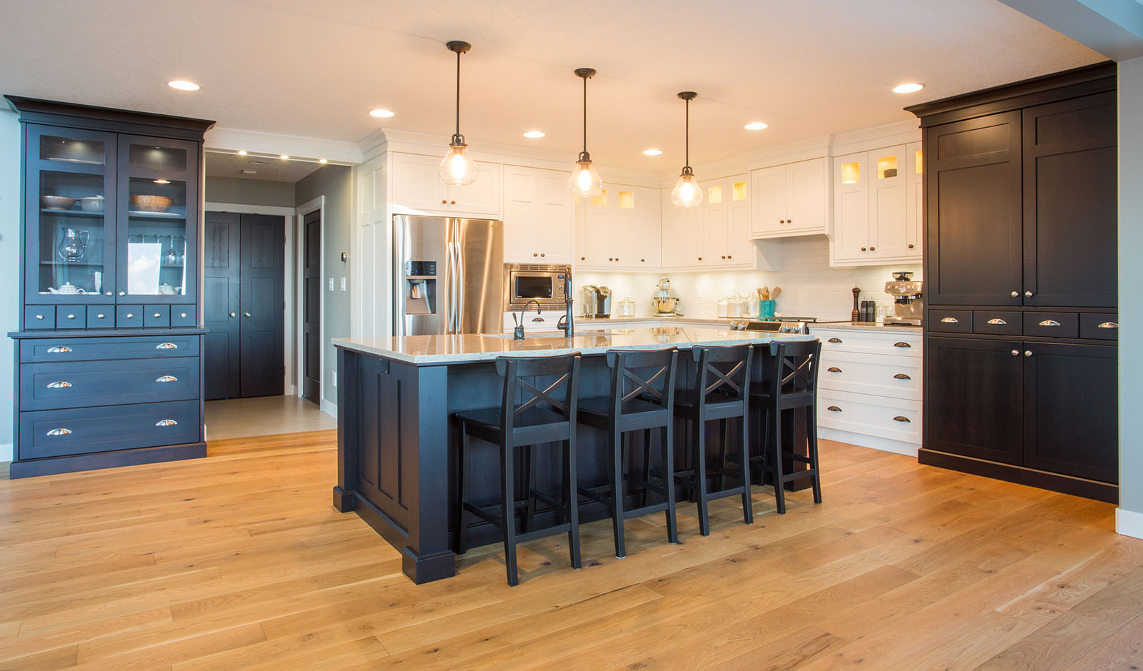 Custom kitchen with built in appliances, hard wood floors, and l