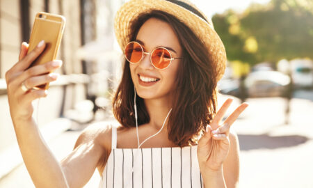 are-you-addicted-to-instagram-here's-how-to-tell-main-image-woman-taking-selfie-making-peace-sign
