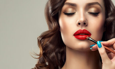beauty-artist-applying-red-lipstick-on-a-woman