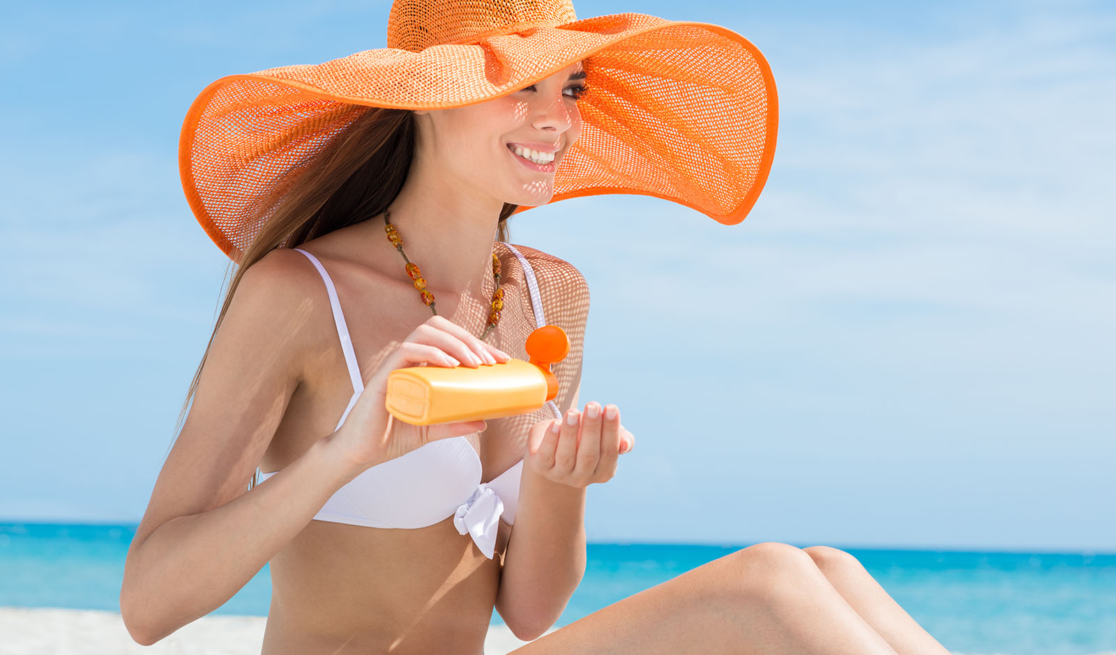 importance-of-sunscreen-woman-applying-sunscreen-at-the-beach-main-image