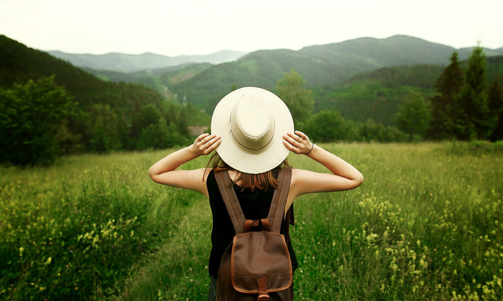 smell-the-roses-things-to-do-when-traveling-girl-in-big-hat-and-backpack-in-field-nature