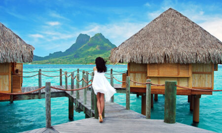 holiday-villas-instead-of-hotels-woman-walking-by-villas-over-the-water-main-image