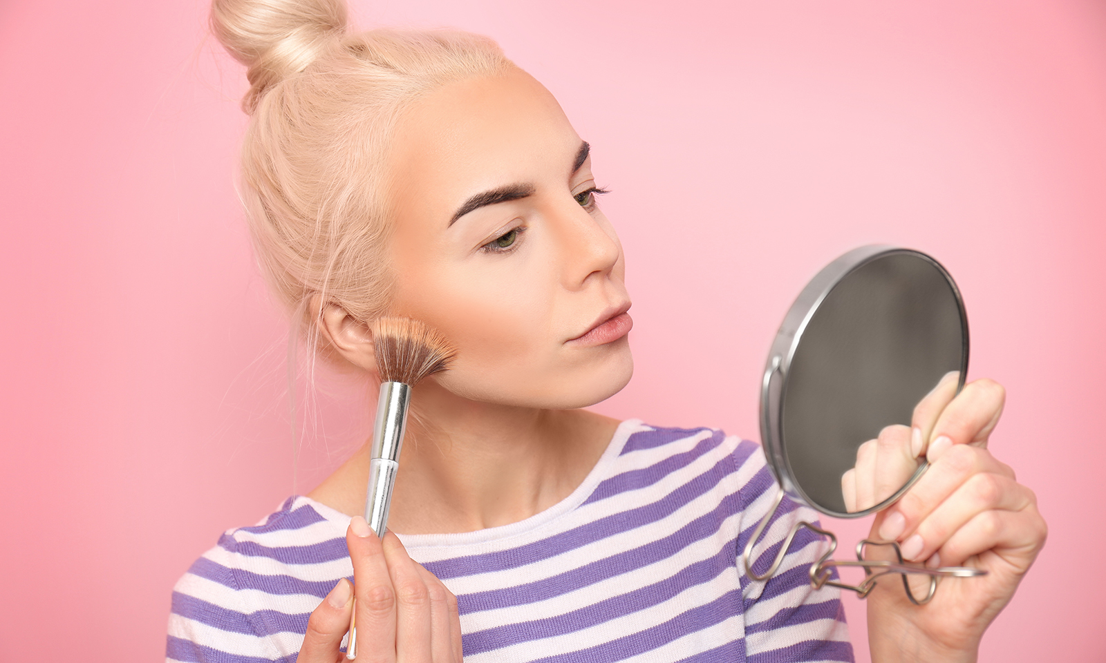 best-makeup-foundations-for-oily-skin-woman-applying-foundation-pink-background