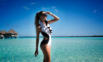 messy-ponytail-looks-for-every-occasion-woman-at-beach-in-water-in-swimsuit-and-ponytail