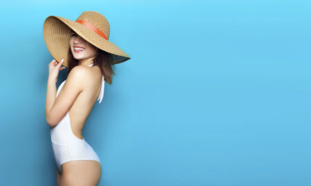 body-polishing-products-and-benefits-gil-with-great-skin-in-bathing-suit-and-hat-blue-background