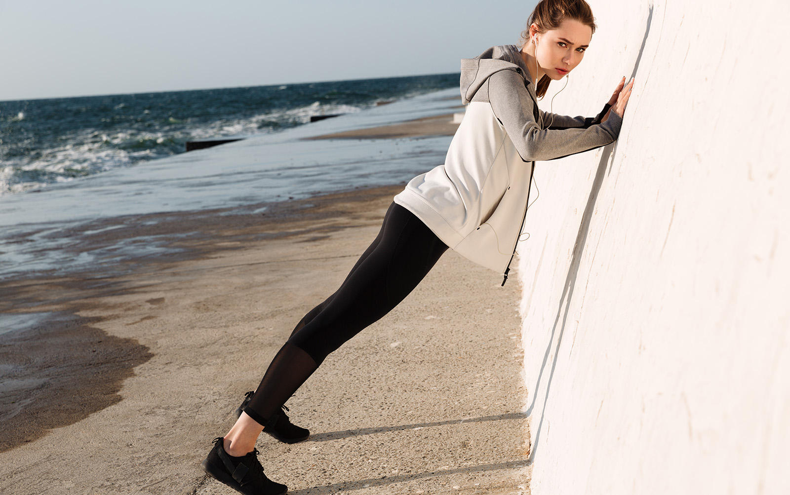 vegan-sneakers-under-$100-you-will-love-woman-working-out-leaning-on-wall