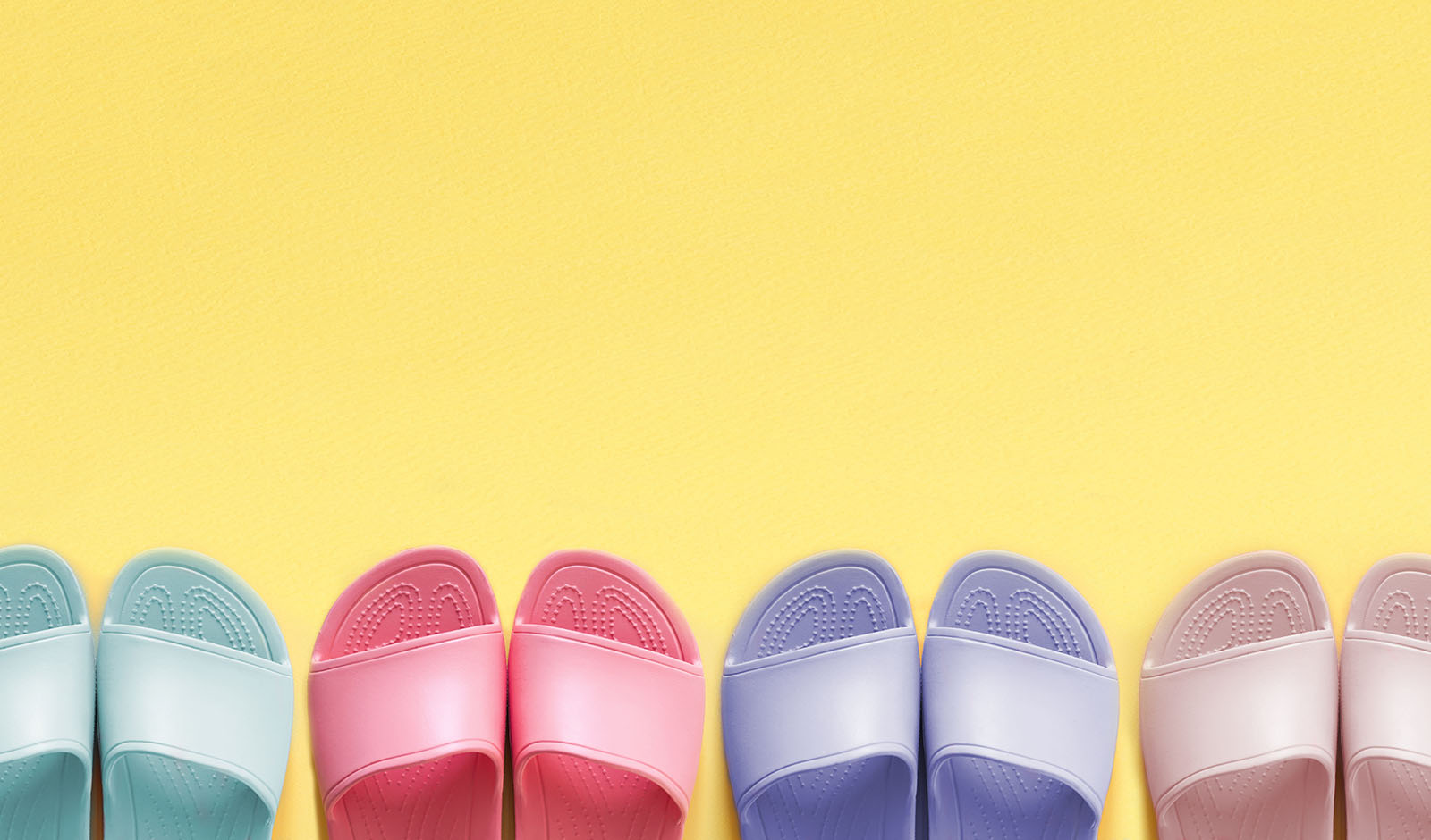 An even row of multi-colored slippers at the bottom of the pictu