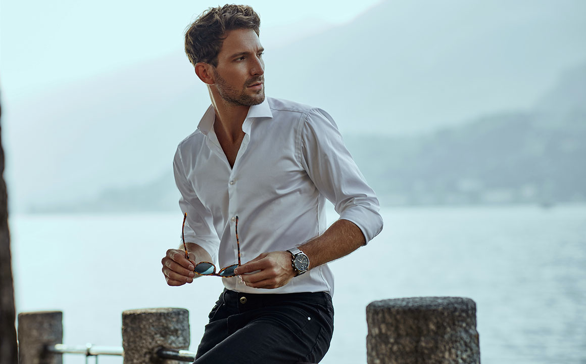 Stylish man in white classic shirt, looking at the mountains vie