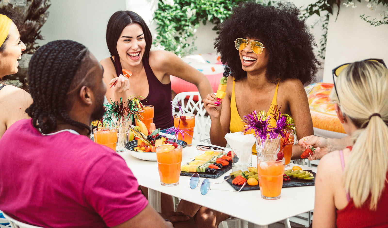 Group of happy multiracial friends talking and laughing having a