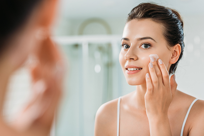 selective focus of smiling young woman applying face cream and l