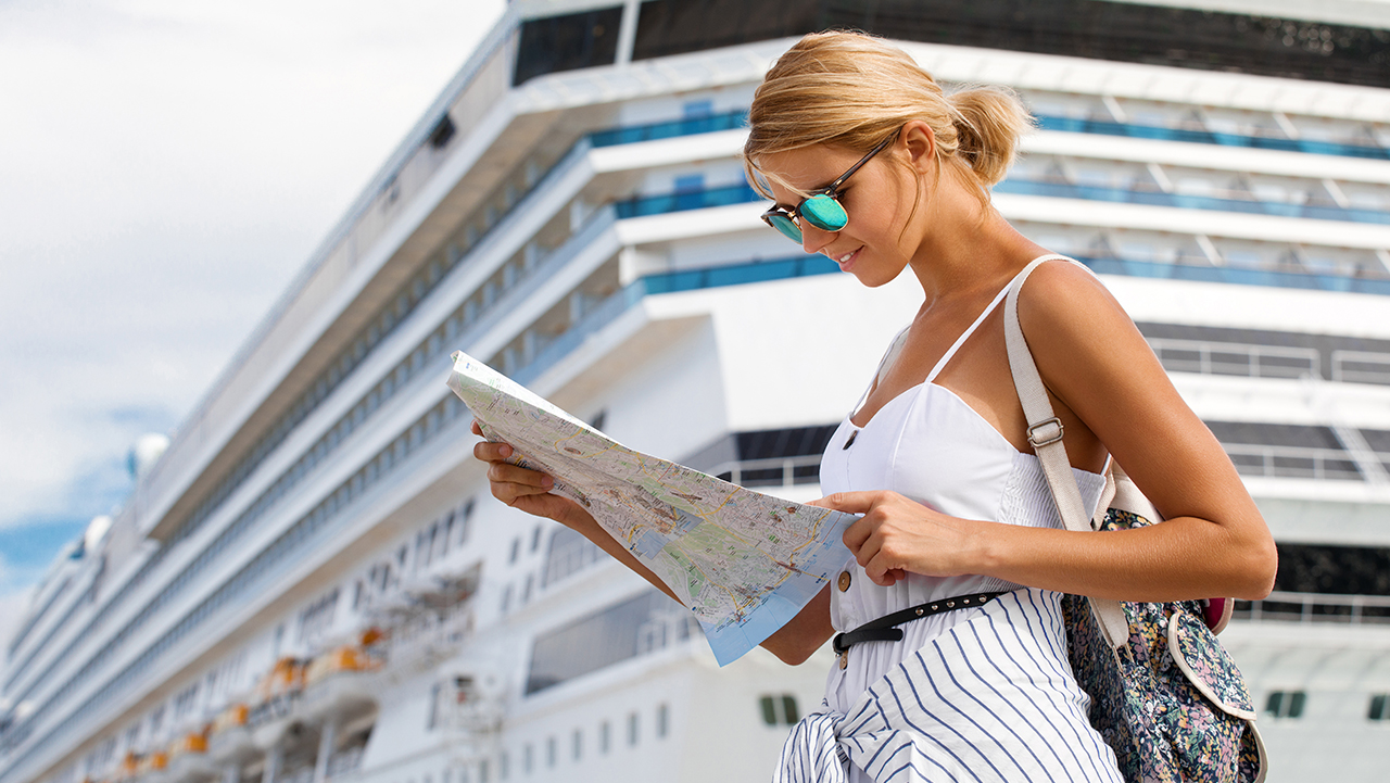 Woman tourist with map, standing in front of big cruise liner, t