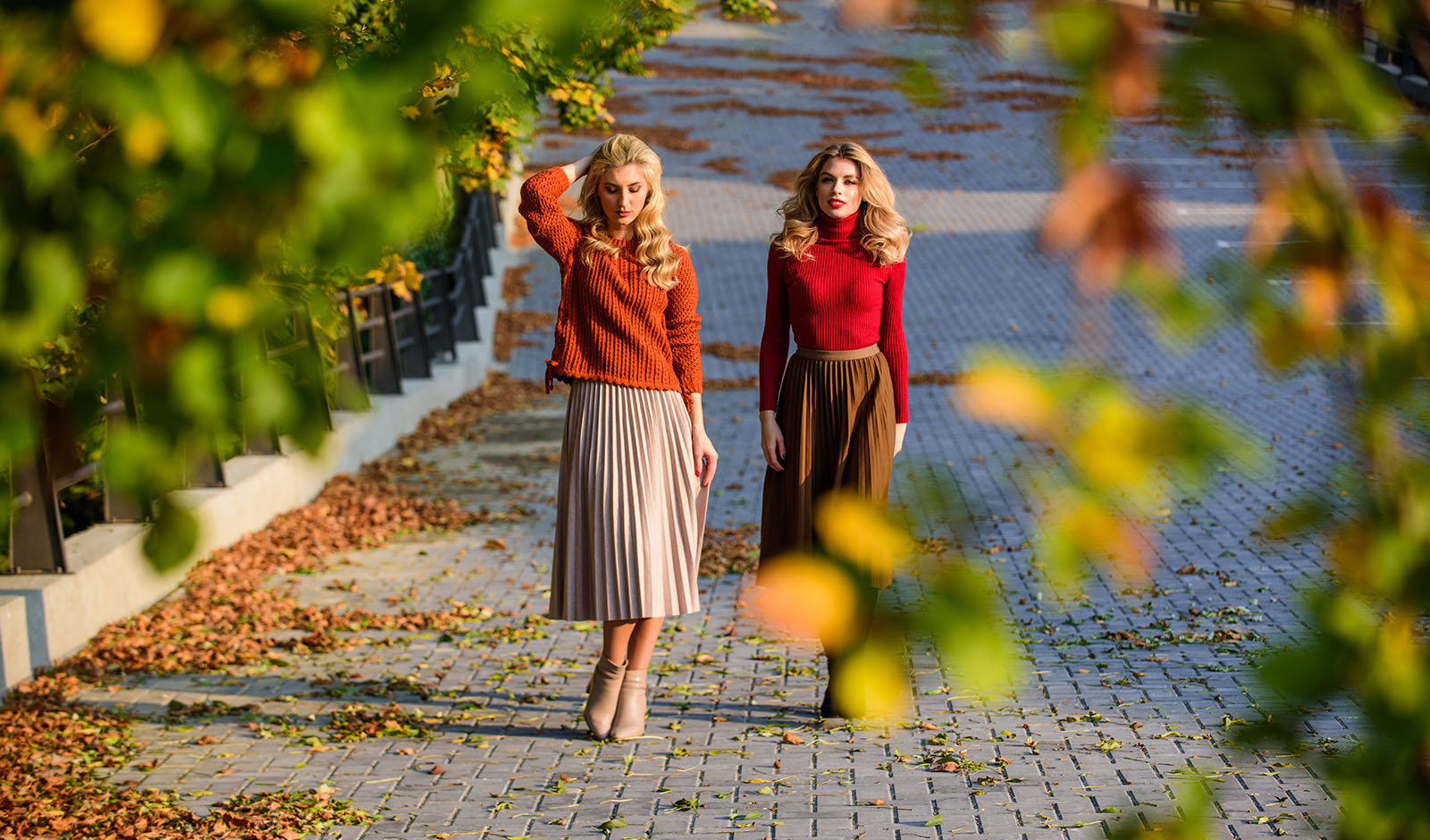 Fall fashion. Adorable ladies enjoy sunny autumn day. Fashionable clothes. Femininity and tenderness. Women walking in autumn park. Pleated skirt fashion trend. Friends girls. Autumn stylish outfit