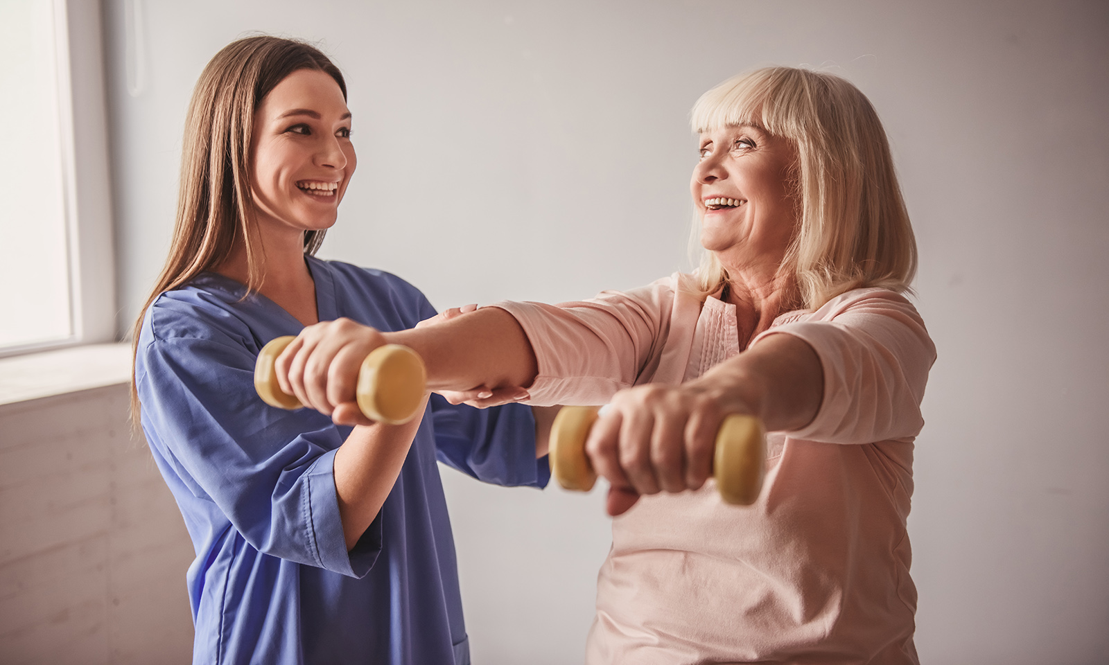 how-a-workout-partner-can-make-youaccountable-for-your-workout-routine-woman-helping-older-woman-with-weights